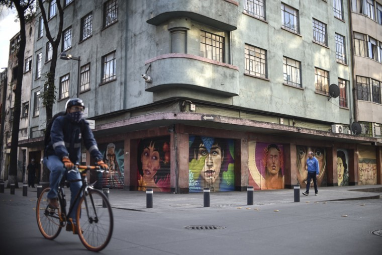 A man rides his bike and another one walks Tuesday past murals in Mexico City. (YURI CORTEZ/AFP/Getty Images)