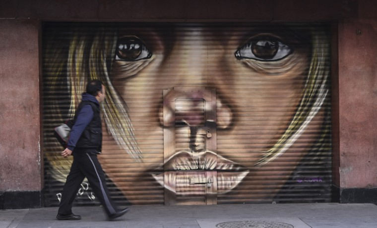 A pedestrian walks past a mural in Mexico City on Tuesday. (YURI CORTEZ/AFP/Getty Images)