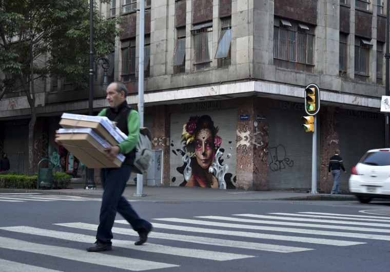 A pedestrian crosses a street Tuesday next to a mural painted as part of a program of the municipality that aims at rescuing public spaces of the historic center in Mexico City. (YURI CORTEZ/AFP/Getty Images)