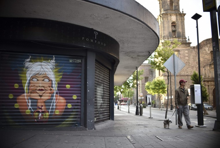 A pedestrian walks his dog past murals commissioned by Mexico City in attempt to bring vitality back to public spaces in the municipality's historic center. (YURI CORTEZ/AFP/Getty Images)