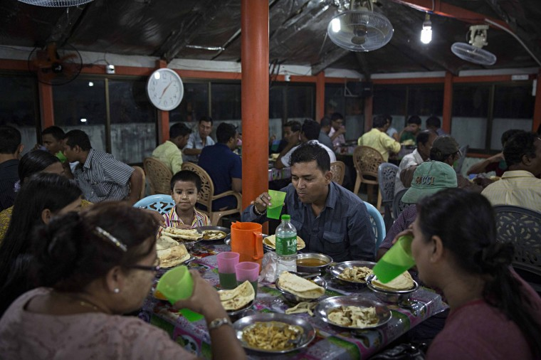Myanmar Muslims partake in Iftari, or breaking fast, after the final evening prayer during Ramadan at the 59th Street Mosque in downtown on June 17, 2016 in Yangon, Burma. Ramadan is the 9th month in the Islamic calendar, observed by the Muslim community as a month of fasting. (Photo by Lauren DeCicca/Getty Images)