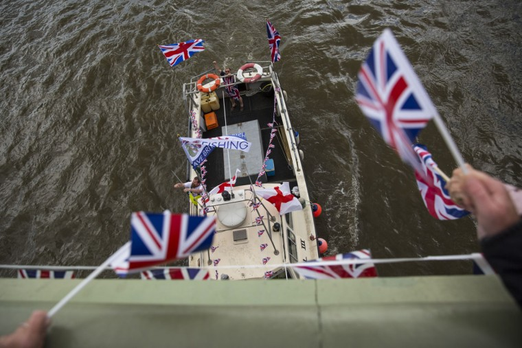 LONDON, ENGLAND - JUNE 15: Supporters wave flags from Westminster Bridge as a boat from the 'Fishing for Leave' campaign joins a flotilla along the Thames River on June 15, 2016 in London, England. The flotilla organised by members of the Fishing for Leave group, who are campaigning to leave the European Union ahead of the referendum on the 23rd of June, was countered by boats representing the 'In' campaign. (Photo by Jack Taylor/Getty Images)