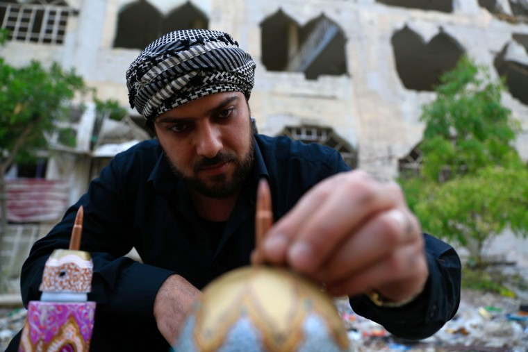 Syrian artist Akram Abu Elfoz puts the last touches on a model of the al-Rawdah mosque which he built using bullet shells, cartridges and war leftovers, ahead of showcasing it next to the destroyed mosque in the rebel-held town of Douma, east of the Syrian capital Damascus, on June 3, 2016. In his most recent project Akram, 37, creates downscaled models of important sites which have been destroyed by the ongoing conflict through using war leftovers, to creatively recreate and document places and buildings that have suffered severe damage. (AFP PHOTO / Sameer Al-Doumy)
