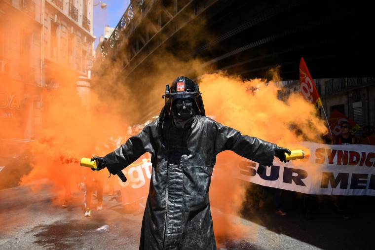 A man wearing a Dark Vador mask holds smoke flares during a demonstration against the French government's planned labour law reforms, on June 2, 2016 in Marseille, southern France. France suffered a third day of rail strikes on June 2, 2016, but fears of transport chaos during the Euro 2016 football tournament eased as airport workers cancelled a walkout and a Paris subway strike had little impact. More demonstrations against the reforms -- which the government says are designed to make France more business-friendly -- took place in major cities on June 2 and workers were back on strike at 16 of the country's 19 nuclear power stations. (Anne-Christine Poujoulat/AFP/Getty Images)