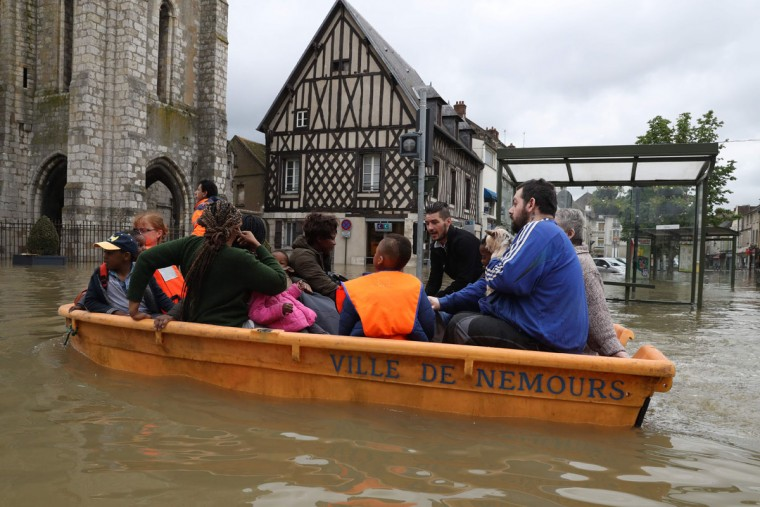A man pulls a small boat transporting inhabitants in a flooded street of Nemours, on June 1, 2016. Torrential downpours have lashed parts of northern Europe in recent days, leaving four dead in Germany, breaching the banks of the Seine in Paris and flooding rural roads and villages. (AFP PHOTO / KENZO TRIBOUILLARD)