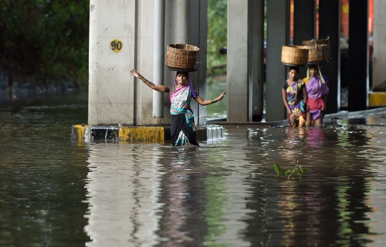 Indian pedestrians balance baskets on their heads as they wade through a flooded street after heavy monsoon rain showers in Mumbai on June 21, 2016. (Punit Paranjpe/AFP/Getty Images)