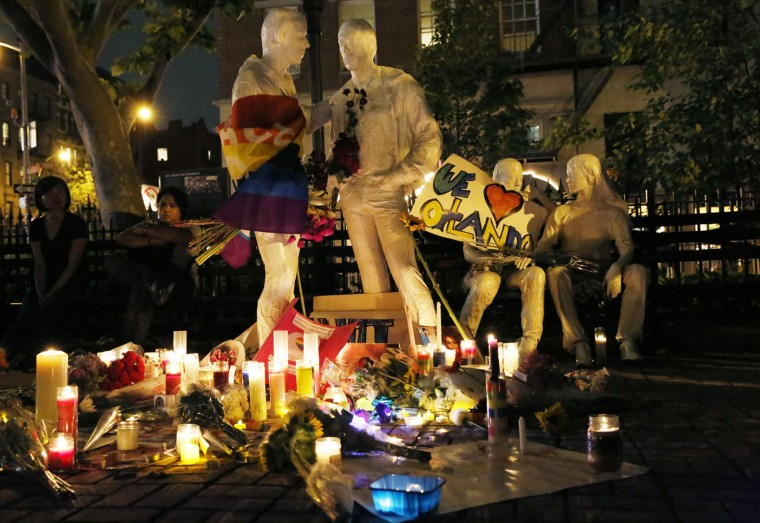 Candles, gay pride flags and flowers adorn statues at Sheridan Square, a memorial for victims of the Stonewall riots, following a vigil and memorial for victims of the Orlando nightclub shooting near the historic Stonewall Inn, a gay bar, Monday, June 13, 2016, in New York. State and city officials, LGBT community members, and others gathered as a show of solidarity with the victims and survivors of the Orlando nightclub shooting, the worst mass shooting in modern U.S. history. (AP Photo/Kathy Willens)