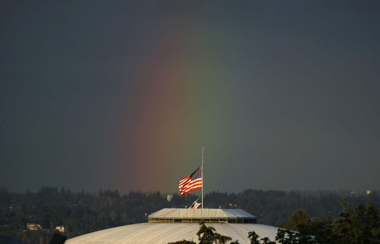 A rainbow appears behind the U.S. flag flying at half-staff on top of the Tacoma Dome, Monday, June 13, 2016, in Tacoma, Wash. Flags across the state were at half-staff Monday to honor the victims of a mass shooting early Sunday at a gay nightclub in Orlando, Florida. (AP Photo/Ted S. Warren)