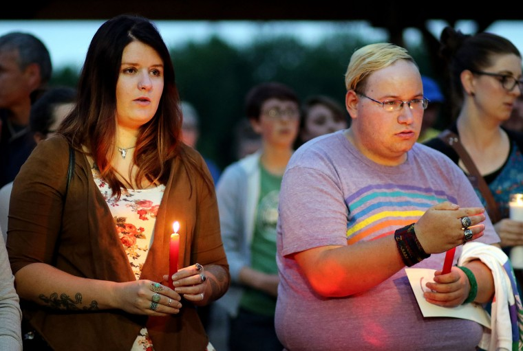 Elizabeth Nowobieliski and Brandon Sorenson sing along in a chant during a vigil for the victims of the Orlando mass shooting at the Phoenix Park Pavilion Monday evening, June 13, 2016, in Eau Claire, Wis. A gunman killed dozens of people in a massacre at a crowded gay nightclub in Orlando on Sunday, making it the deadliest mass shooting in modern U.S. history. (Marisa Wojcik/The Eau Claire Leader-Telegram via AP)