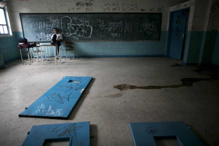 In this June 1, 2016 photo, a student sits on a teacher's desk inside what was once a classroom, where doors lay on the floor as well as urine, at a public high school in Caracas, Venezuela. The social and economic chaos stalking Venezuela is ripping apart its once-enviable school system, robbing poor students of what would otherwise be their best chance to escape lives fast becoming unbearable. (AP Photo/Ariana Cubillos)