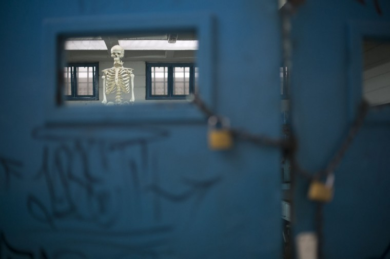 In this June 1, 2016 photo, a skeleton hangs inside a classroom used to teach evolution, locked up to keep teaching material from getting stolen, at a public high school in Caracas, Venezuela. The school locks the heavy metal gate at its sole entrance each day, making the building feel even more like a prison but students seem to be glad for the extra protection. (AP Photo/Ariana Cubillos)
