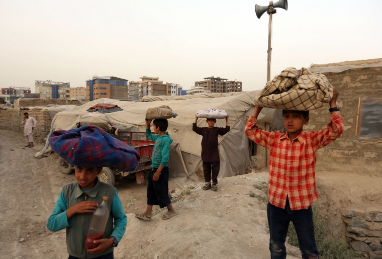 Afghan boys carry traditional Afghani bread, known as Bolani, to sell, during of the holy fasting month of Ramadan, in Kabul, Afghanistan, Wednesday, June 15, 2016. Muslims across the world are observing the holy fasting month of Ramadan, when they refrain from eating, drinking and smoking from dawn to dusk. (AP Photo/Rahmat Gul)