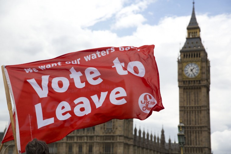 "Leave supporters hold flags as they stand on Westminster Bridge during an EU referendum campaign stunt in which a flotilla of boats supporting ""Leave"" sailed up the River Thames outside the Houses of Parliament in London, Wednesday, June 15, 2016. A flotilla of boats protesting EU fishing polices has sailed up the River Thames to the Houses of Parliament as part of a campaign backing Britain's exit from the European Union. The flotilla was greeted by boats carrying ""remain"" supporters. (AP Photo/Matt Dunham)"