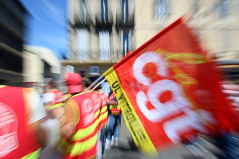 Protestors holding the flag of the CGT Union (Confederation Generale du Travail), demonstrate in Marseille, southern France, Thursday, June 2, 2016. Several thousand protestors are demonstrating during a day of strikes and protest against the law job government reform. (AP Photo/Claude Paris)