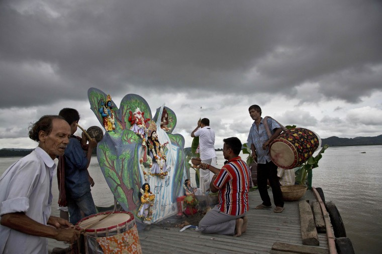 People pray before an idol of Goddess Ganges before immersing it in Brahmaputra river as monsoon clouds envelop the sky in Gauhati, India , Friday, June 17, 2016. After a couple of years of deficient monsoon, the Indian meteorological department has predicted a wetter than normal monsoon season which will be a relief to the farmers since most of agriculture in India is largely dependent on rain. (AP Photo/ Anupam Nath)