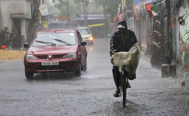 A man rides a bicycle as it rains in Kolkata, India, Thursday, June 16, 2016. After a couple of years of deficient monsoon, the Indian meteorological department has predicted a wetter than normal monsoon season which will be a relief to the farmers as most of agriculture in India is largely dependent on rain. (AP Photo/ Bikas Das)