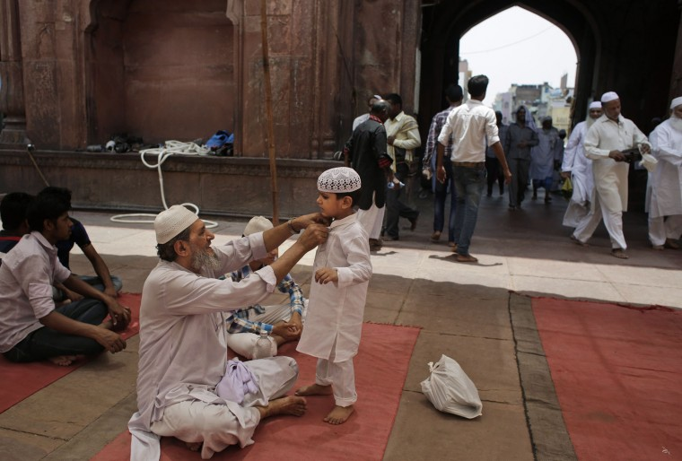 An Indian Muslim man grooms a young boy as they wait to offer prayers on the second Friday of the holy fasting month of Ramadan at Jama Masjid in New Delhi, India, Friday, June 17, 2016. Islam's holiest month is a period of intense prayer, self-discipline, dawn-to-dusk fasting and nightly feasts. (AP Photo/Altaf Qadri)