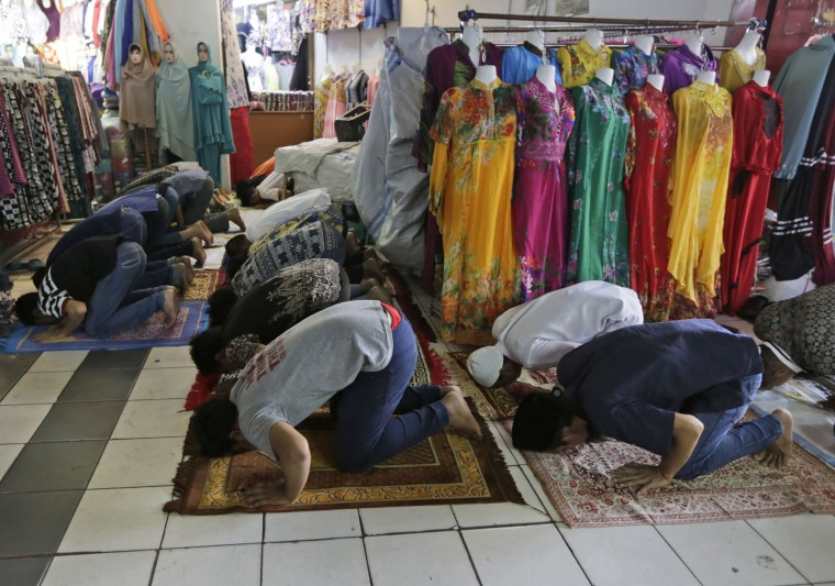 Muslim men perform Friday prayer near mannequins displaying Islamic clothing at a market in Jakarta, Indonesia, Friday, June 17, 2016. Muslims across the world are observing the holy fasting month of Ramadan, when they refrain from eating, drinking and smoking from dawn to dusk. (AP Photo/Dita Alangkara)
