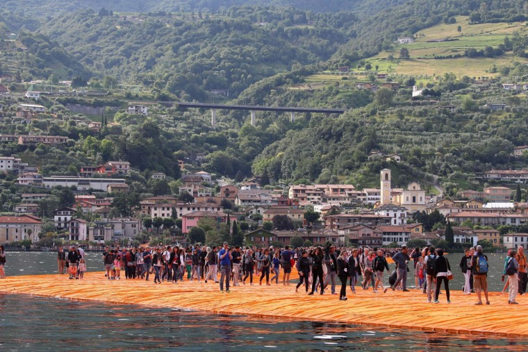 People walk on the installation 'The Floating Piers' by Bulgarian-born artist Christo Vladimirov Yavachev known as Christo, on the Lake Iseo, northern Italy, Saturday, June 18, 2016. (Filippo Venezia/Ansa via AP)