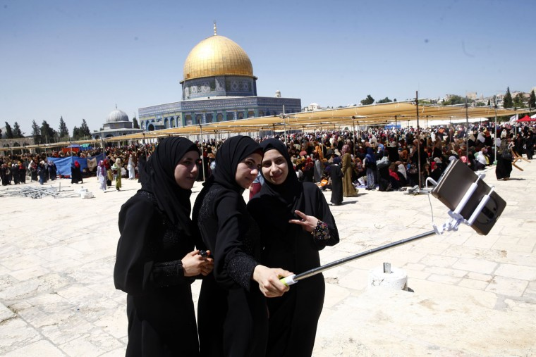 Palestinian women take a picture during the Muslim holy month of Ramadan at the Dome of the Rock Mosque in the Al Aqsa Mosque compound in Jerusalem's Old City, Friday, June 17, 2016. (AP Photo/Mahmoud Illean)