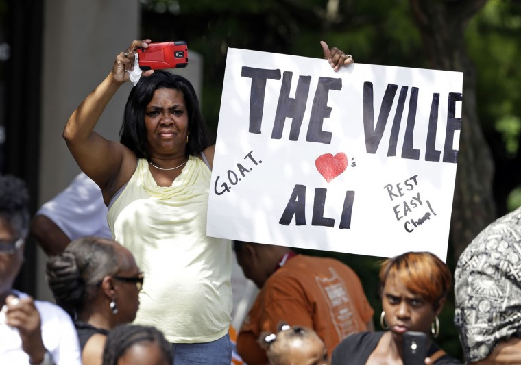 A mourner holds a sign as the funeral procession for Muhammad Ali makes its way down Muhammad Ali Boulevard in Louisville, Ky. Friday, June 10, 2016. (AP Photo/Michael Conroy)
