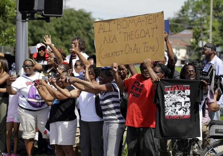 Crowds line the route and cheer as the procession passes led by the hearse carrying the body of Muhammad Ali, Friday, June 10, 2016, in Louisville, Ky. (AP Photo/Darron Cummings)
