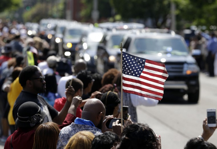 A mourner holds an American flag as the funeral procession for Muhammad Ali makes its way down Muhammad Ali Boulevard in Louisville, Ky. Friday, June 10, 2016. (AP Photo/Michael Conroy)