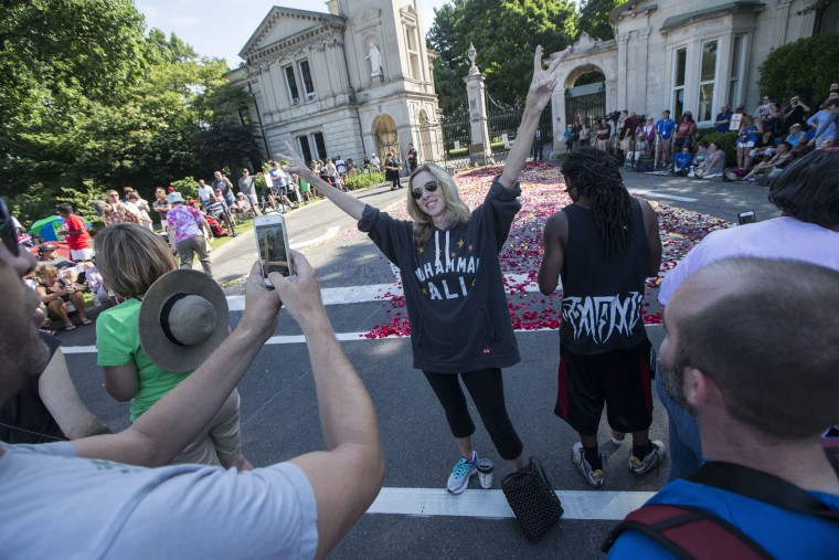 Carrie Williamson, of Louisville, poses for a photograph as spectators wait for the arrival of Muhammad Ali's funeral procession to enter Cave Hill Cemetery, Friday, June 10, 2016, in Louisville, Ky. Ali died last Friday at age 74 after a long battle with Parkinson's disease. (AP Photo/John Minchillo)