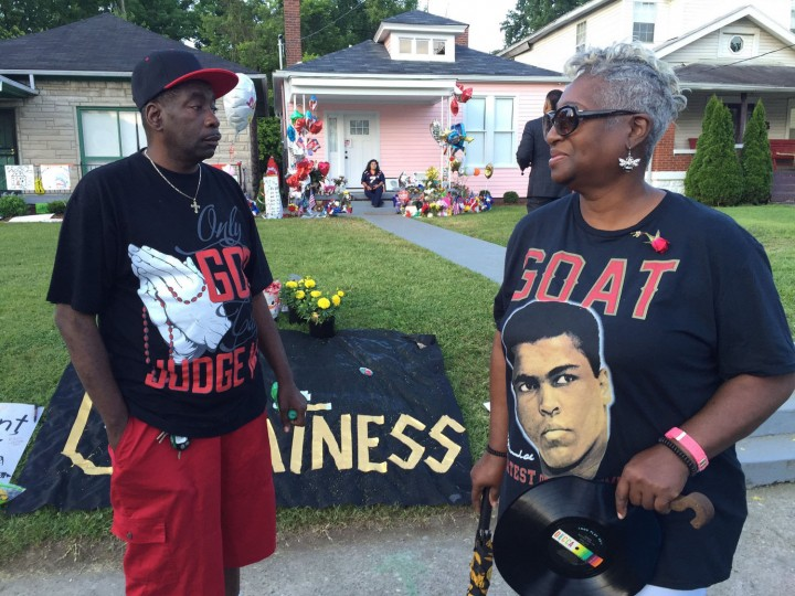 Area residents stand in front of Muhammad Ali's boyhood home Friday, June 10, 2016, in Louisville, Ky. Ali's funeral procession is scheduled to pass by the house later in the day. (Alton Strupp/The Courier-Journal via AP)