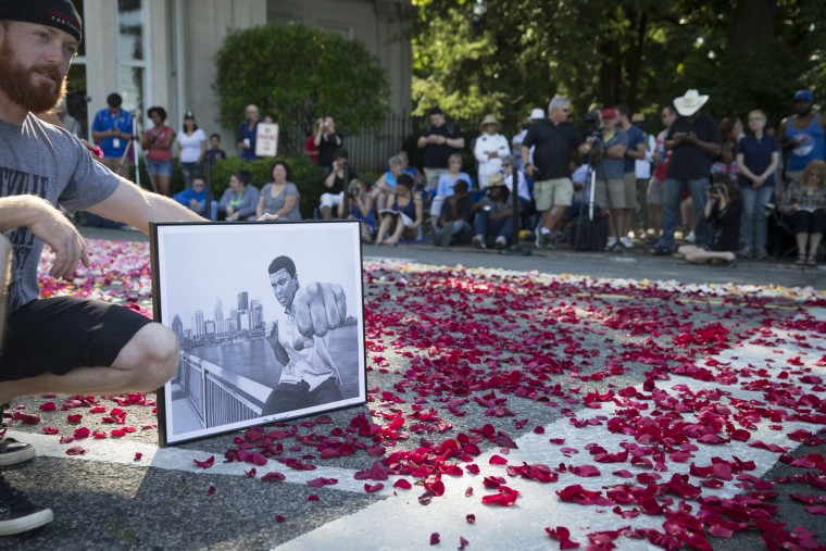 Nick Smith, of Louisville, poses for a photograph holding a drawing of Muhammad Ali as spectators wait for the arrival of Ali's funeral procession to enter Cave Hill Cemetery, Friday, June 10, 2016, in Louisville, Ky. Ali died last Friday at age 74 after a long battle with Parkinson's disease. (AP Photo/John Minchillo)