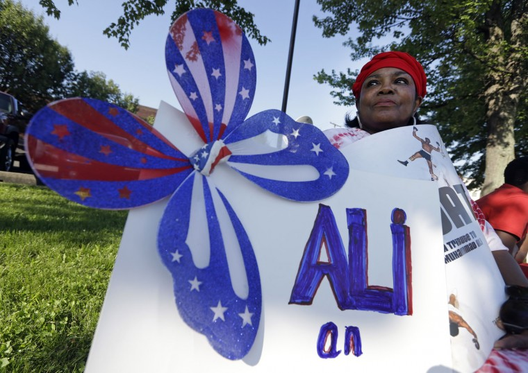 Frances Woods holds a sign saluting Muhammad Ali as she awaits his funeral procession to make its way down Muhammad Ali Boulevard in Louisville, Ky. Friday, June 10, 2016. (AP Photo/Michael Conroy)
