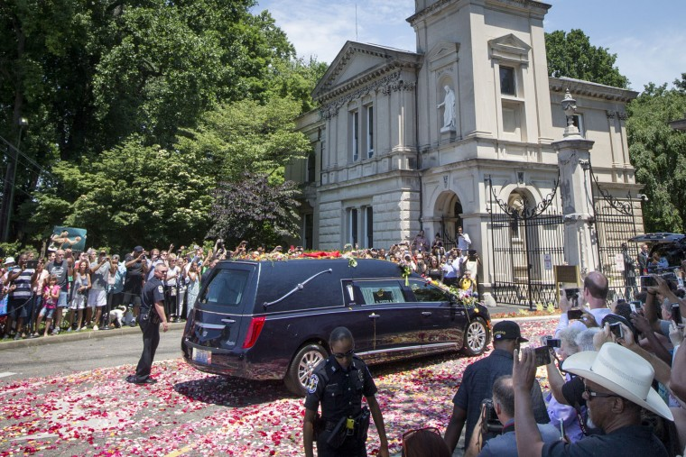 The hearse carrying Muhammad Ali arrives as spectators watch his funeral procession enter Cave Hill Cemetery, Friday, June 10, 2016, in Louisville, Ky. (AP Photo/John Minchillo)