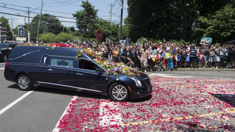 Flowers pile up on the hearse carrying Muhammad Ali as spectators watch his funeral procession enter Cave Hill Cemetery, Friday, June 10, 2016, in Louisville, Ky. Ali died last Friday at 74 after a long battle with Parkinson's disease. (AP Photo/John Minchillo)