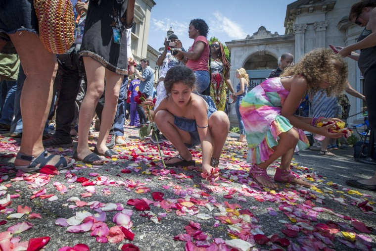 Children and spectators collect flowers from the road that Muhammad Ali's funeral procession passed along to enter Cave Hill Cemetery, Friday, June 10, 2016, in Louisville, Ky. (AP Photo/John Minchillo)