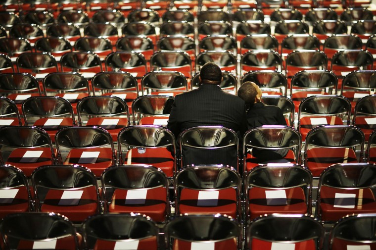 Stephfon Moran, left, sits with his grandson Kevin Slaughter, 9, as they wait for Muhammad Ali's memorial service to begin Friday, June 10, 2016, in Louisville, Ky. (AP Photo/David Goldman)