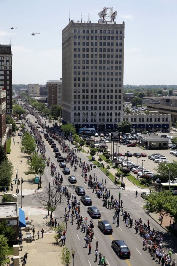 Muhammad Ali's funeral procession passes as onlookers line the street Friday, June 10, 2016, in Louisville, Ky. (AP Photo/Jeff Roberson)