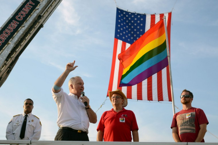 From left, Tampa Fire Rescue Chief Tom Forward, Tampa Mayor Bob Buckhorn, Tampa Pride President Carrie West and GaYbor President Ernie Webb stand on a float during Mayor Buckhorn's address at a candlelight vigil in Tampa, Fa., Monday, June 13, 2016. Vigils, rallies and marches are being held around the country Monday for the victims of early Sunday's deadly attack at a gay nightclub in Orlando. (Chris Urso/Tampa Bay Times via AP)
