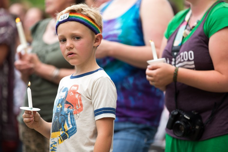 Emerson Wyzgoski, 7, of Kalamazoo, holds a candle at a candlelight vigil at Bronson Park hosted by Kalamazoo Gay Lesbian Resource Center honoring the victims of the mass shooting at Pulse nightclub in Orlando, Monday, June 13, 2016 in Kalamazoo, Mich. A gunman has killed dozens of people in a massacre at a crowded gay nightclub in Orlando, Fla. on Sunday, making it the deadliest mass shooting in modern U.S. history. (Bryan Bennett/Kalamazoo Gazette-MLive Media Group via AP)