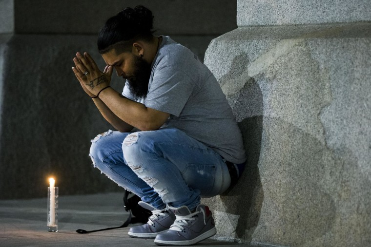 Lou Berrios bows his head as he gathers with others for a vigil in memory of the victims of the Orlando, Fla., worst mass shooting in modern U.S. history, Monday, June 13, 2016, at City Hall in Philadelphia. A gunman opened fire inside a crowded gay nightclub early Sunday, before dying in a gunfight with SWAT officers, police said. (AP Photo/Matt Rourke)