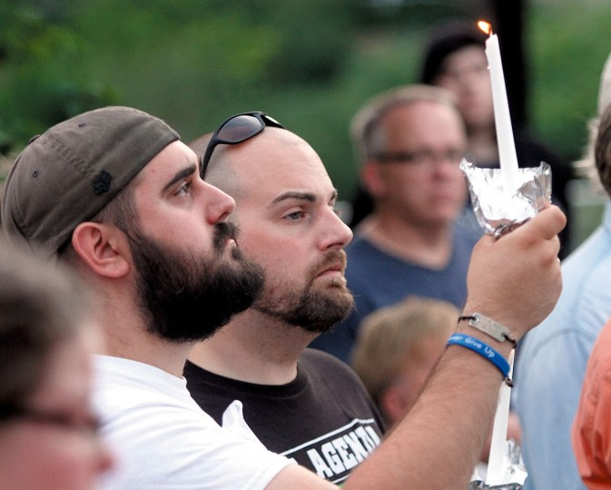Phil and Matthew Verso hold a candle a high in the air in remembrance of victims of the Orlando mass shooting victims during a candlelight vigil held on the Maryville greenbelt, Monday, June 13, 2016, in Maryville, Tenn. A gunman killed dozens of people in a massacre at a crowded gay nightclub in Orlando on Sunday, making it the deadliest mass shooting in modern U.S. history. (Tom Sherlin/The Daily Times via AP)