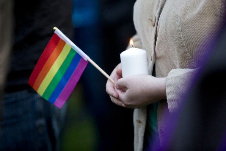 A woman holds a candle and a pride flag during a vigil for the Orlando shooting victims at Memorial Park in Provo, Monday, June 13, 2016. Over 200 people attended the event which featured speakers from local groups like PFLAG and Resilient Hope. (Sammy Jo Hester/The Daily Herald via AP)