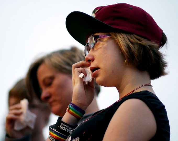 Phoebe Darr, 14, of Elk Mound, Wis., tears up as the names of those killed in the Orlando, Fla., mass shooting are read at a candlelight vigil at the Phoenix Park Pavilion Monday evening, June 13, 2016, in Eau Claire, Wis. A gunman killed dozens of people in a massacre at a crowded gay nightclub in Orlando on Sunday, making it the deadliest mass shooting in modern U.S. history. (Marisa Wojcik/The Eau Claire Leader-Telegram via AP)