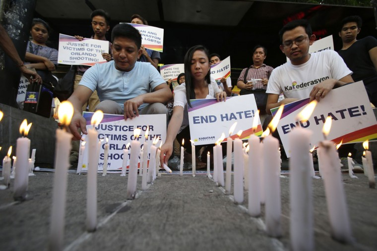 Filipino youth activists light candles as they hold slogans during a gathering in solidarity with victims of the mass shooting at the Pulse nightclub in Orlando, Florida during a gathering in Manila, Philippines on Tuesday June 14, 2016. The group calls for justice for the victims of the mass shooting. (AP Photo/Aaron Favila)