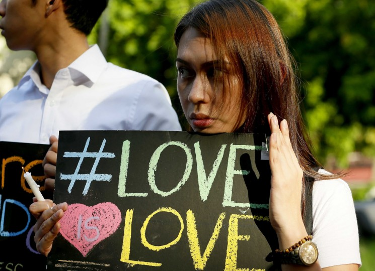 A Filipino member of the LGBT (Lesbian, Gay, Bisexual, Transgender) group holds a placard during a vigil to pay tribute to the victims of the Orlando, Fla. mass shooting Tuesday, June 14, 2016 at the University of the Philippines campus in suburban Quezon city northeast of Manila, Philippines. A gunman, later identified as Omar Mateen, opened fire inside a crowded gay nightclub in Orlando, Fla. early Sunday before dying in a gunfight with responding SWAT officers, authorities said. (AP Photo/Bullit Marquez)