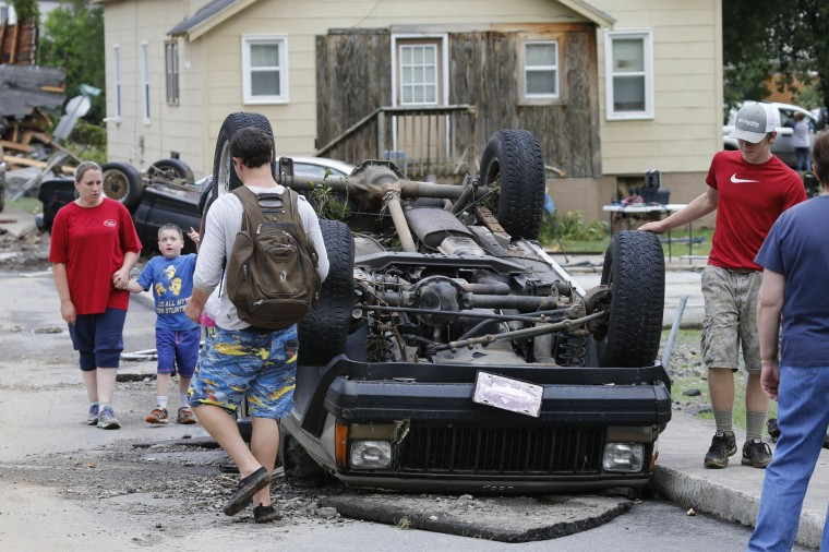 Residents walk past an overturned car as the cleanup begins from severe flooding in White Sulphur Springs, W. Va., Friday, June 24, 2016. A deluge of 9 inches of rain on parts of West Virginia destroyed or damaged more than 100 homes and knocked out power to tens of thousands of homes and businesses. (AP Photo/Steve Helber)