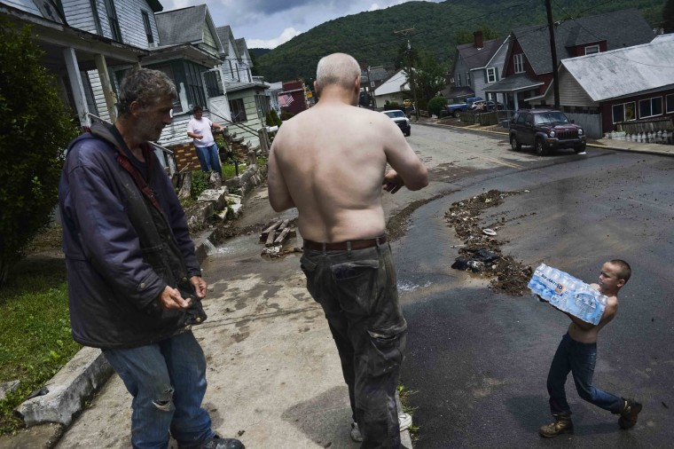 James Tinnel, left, and other residents receive cases of bottled water from the volunteer fire department during cleanup after severe flooding in Richwood, W.Va. on Friday June 24, 2016. (Christian Tyler Randolph/Charleston Gazette-Mail via AP)
