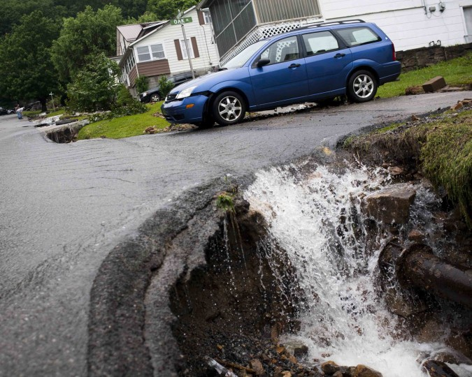 Water rushes past a damaged car and into a chasm of exposed piping created by flood damage on Oarkford Avenue in Richwood, W.Va. on Friday June 24, 2016. (Christian Tyler Randolph/Charleston Gazette-Mail via AP)
