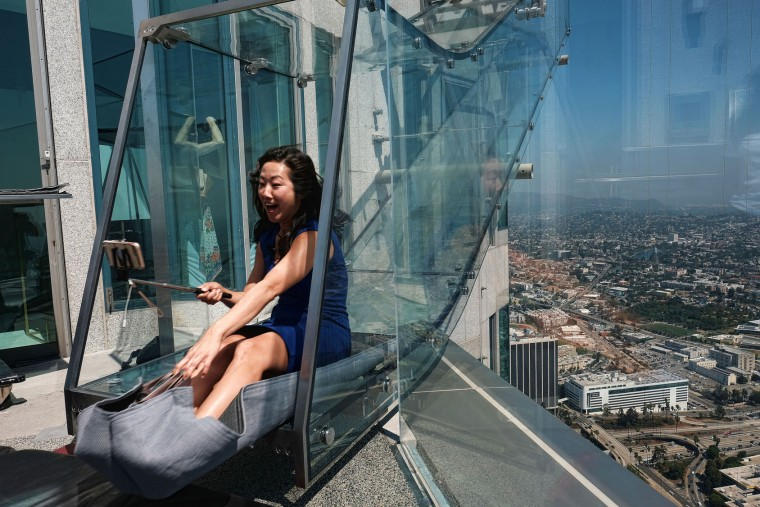 Jo Kqon, a reporter with KFI radio Los Angeles, takes a selfie as she rides down a glass slide during a media preview at the U.S. Bank Tower building in downtown Los Angeles on Thursday, June 23, 2016. Starting this weekend, thrill-seekers can begin taking the Skyslide, a 1,000 feet high slide perched outside of the tallest skyscraper west of the Mississippi. (AP Photo/Richard Vogel)