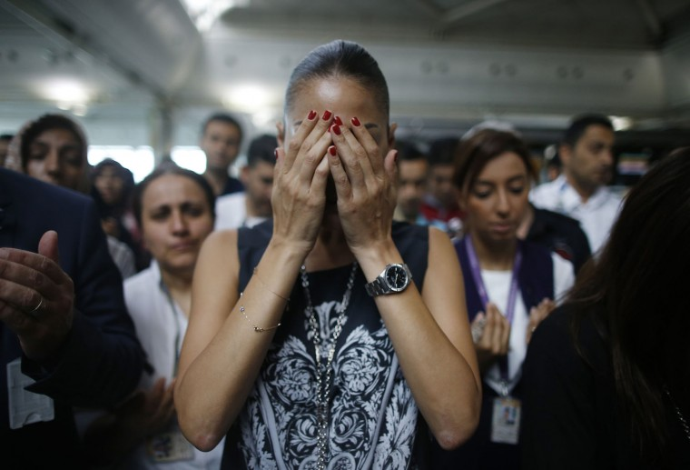 A woman reacts as family members, colleagues and friends of the victims of Tuesday blasts gather for a memorial ceremony at the Ataturk Airport in Istanbul, Thursday, June 30, 2016. A senior Turkish official on Thursday identified the Istanbul airport attackers as a Russian, Uzbek and Kyrgyz national hours after police carried out sweeping raids across the city looking for Islamic State suspects. Tuesday's gunfire and suicide bombing attack at Ataturk Airport killed dozens and injured over 200. Turkish authorities have banned distribution of images relating to the Ataturk airport attack within Turkey. (AP Photo/Emrah Gurel)