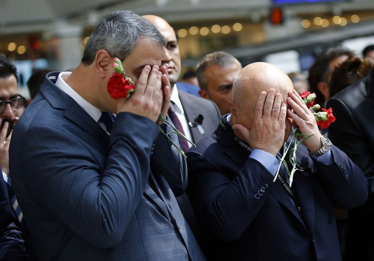 Men react as family members, colleagues and friends of the victims of Tuesday blasts gather for a memorial ceremony at the Ataturk Airport in Istanbul, Thursday, June 30, 2016. A senior Turkish official on Thursday identified the Istanbul airport attackers as a Russian, Uzbek and Kyrgyz national hours after police carried out sweeping raids across the city looking for Islamic State suspects. Tuesday's gunfire and suicide bombing attack at Ataturk Airport killed dozens and injured over 200. Turkish authorities have banned distribution of images relating to the Ataturk airport attack within Turkey. (AP Photo/Emrah Gurel)